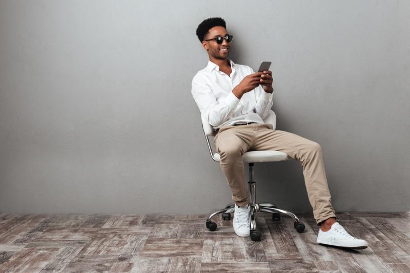 Black Man Using Phone Smiling Chair