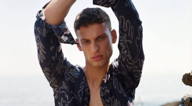 Sporting an open printed shirt, David Trulik stars in Giorgio Armani's summer 2021 men's campaign.
