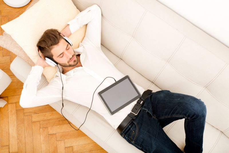 Man Laying Down on Couch Listening to Music with Headphones