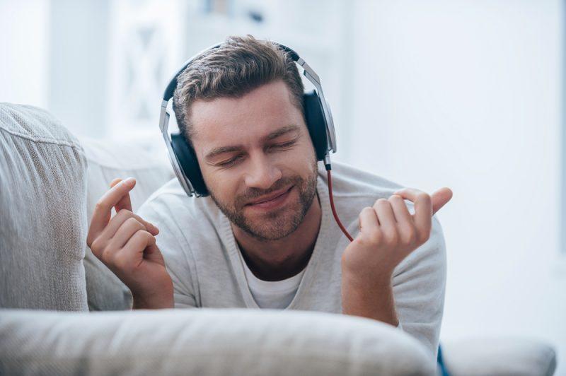 Man Smiling Listening to Music on Headphones