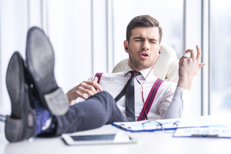 Man at Desk in Office Listening to Music