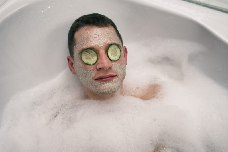 Man with Face Mask Cucumbers Bubble Bath