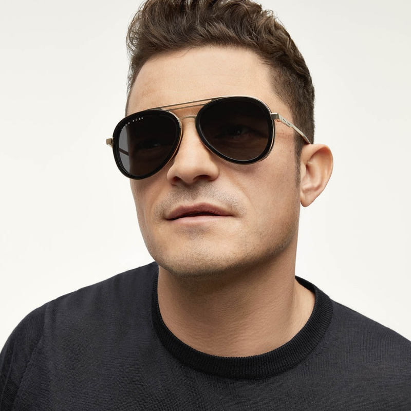 Looking to stand out from the crowd, Orlando Bloom wears BOSS's triple-bridge sunglasses with black and gold-tone frames.