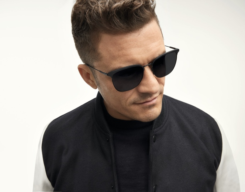 A cool, modern vision, Orlando Bloom rocks BOSS's lightweight sunglasses in matte black with gray lenses.