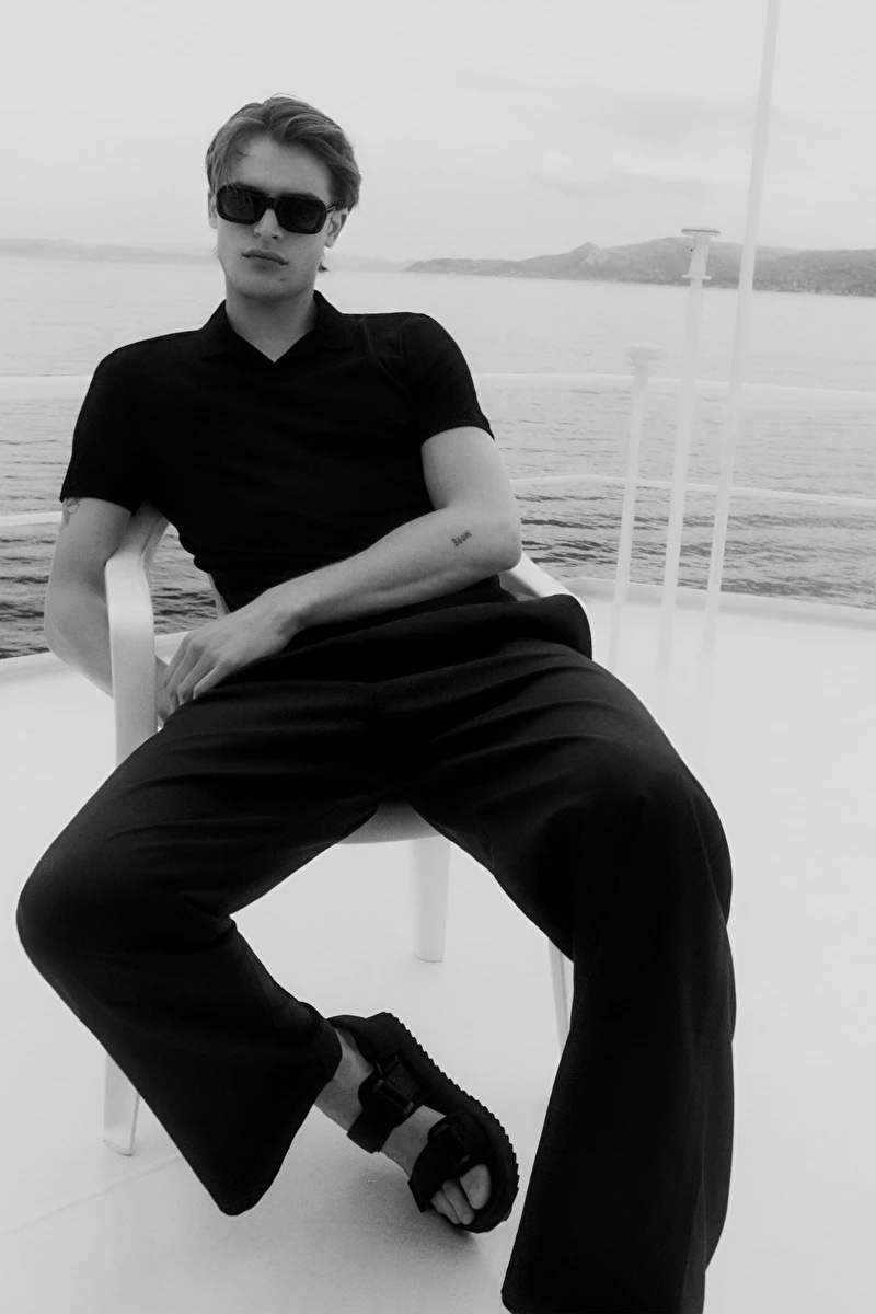 Yachting, Parker Van Noord relaxes in a black open collar polo shirt, drawstring wide-leg pants, and strap sandals by COS.