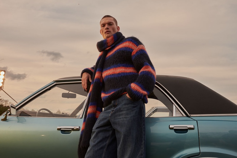 William Los models a matching striped sweater and scarf from Kenzo.