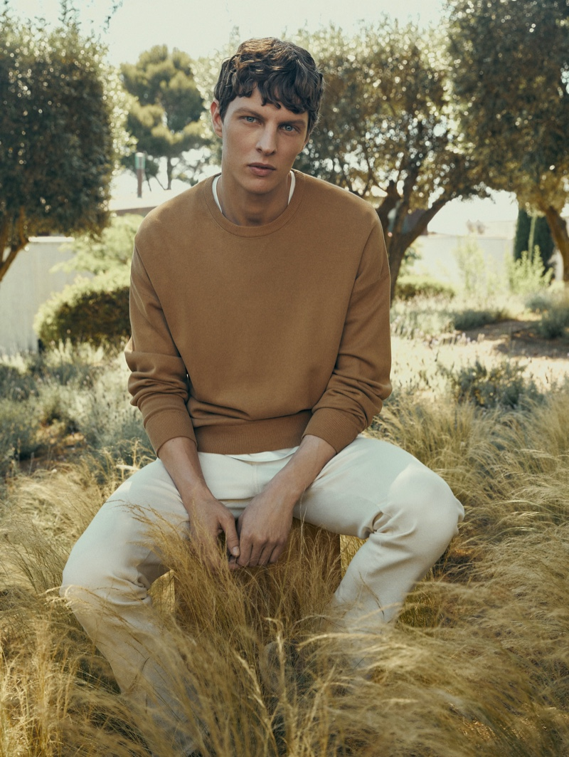 Enjoying the sights of nature, Tim Schuhmacher wears a crewneck sweater with white pants by Massimo Dutti.