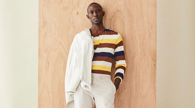 Front and center, Armando Cabral dons a long-sleeve striped pocket tee with a neutral-colored jacket and pants from Todd Snyder.