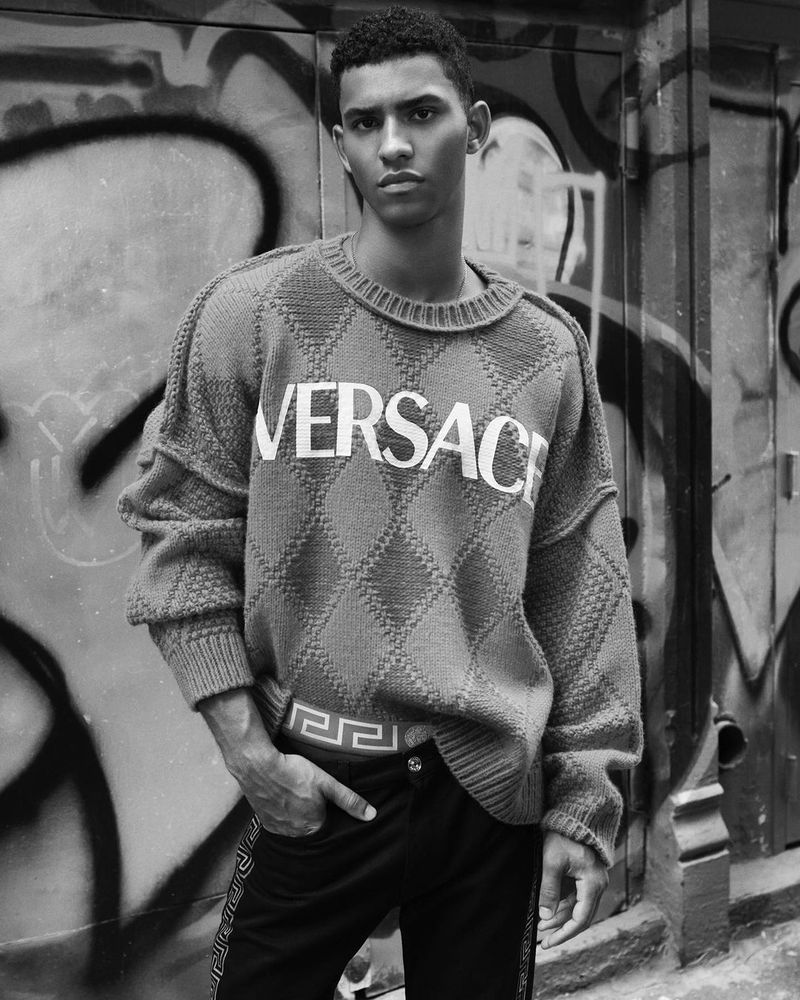 Jan Carlos Diaz sports an argyle Versace sweater as he poses for a photo in SoHo, New York.