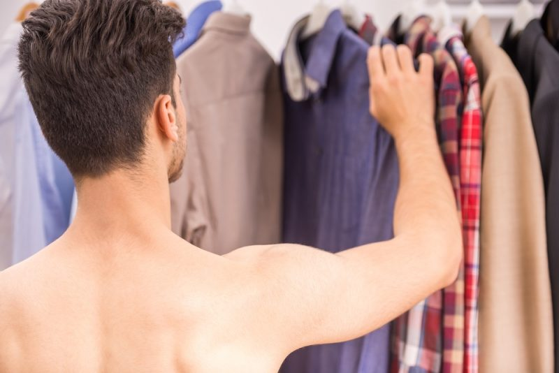 Young Man Looking Through Clothes Shirtless