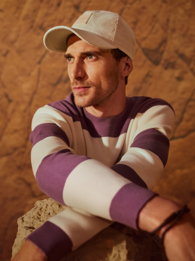 Going casual, Clément Chabernaud models a purple and white striped sweater with a corduroy cap for BOSS's fall-winter 2021 men's campaign.