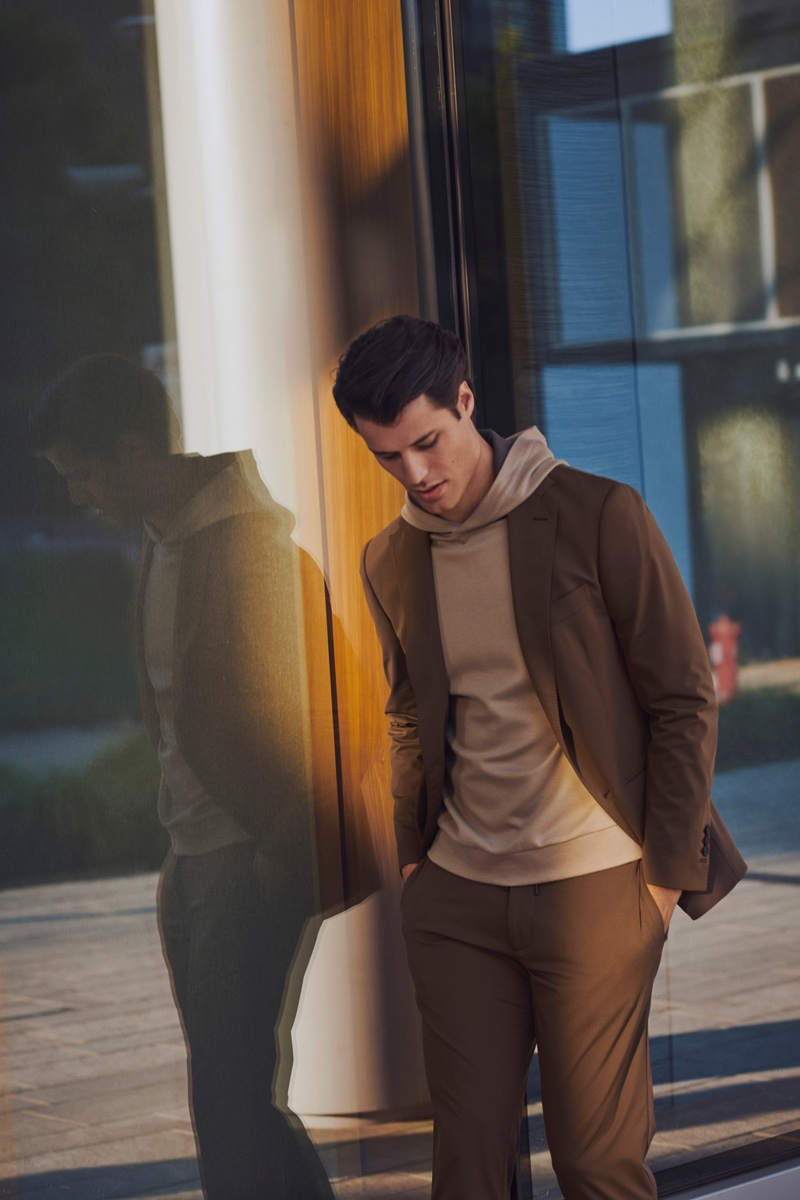 Embracing shades of brown, Emilio Flores wears a suit and hooded pullover from Boggi Milano.
