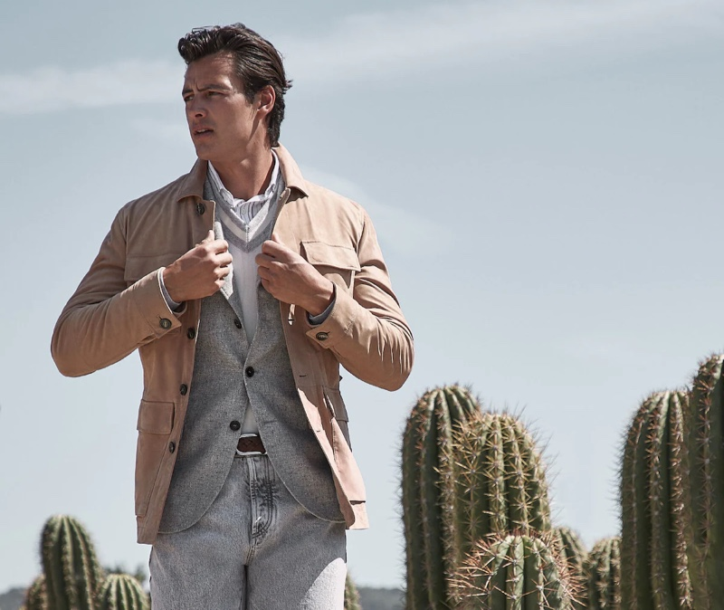 Mixing neutrals, Harry Gozzett dons a four pocket jacket over a blazer, v-neck sweater, and striped shirt with denim jeans by Brunello Cucinelli.