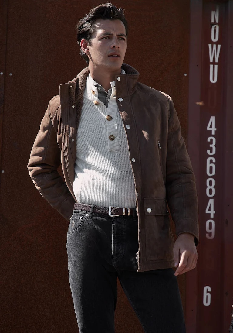 Front and center, Harry Gozzett wears a Brunello Cucinelli ribbed sweater with a shearling jacket and dark denim jeans.