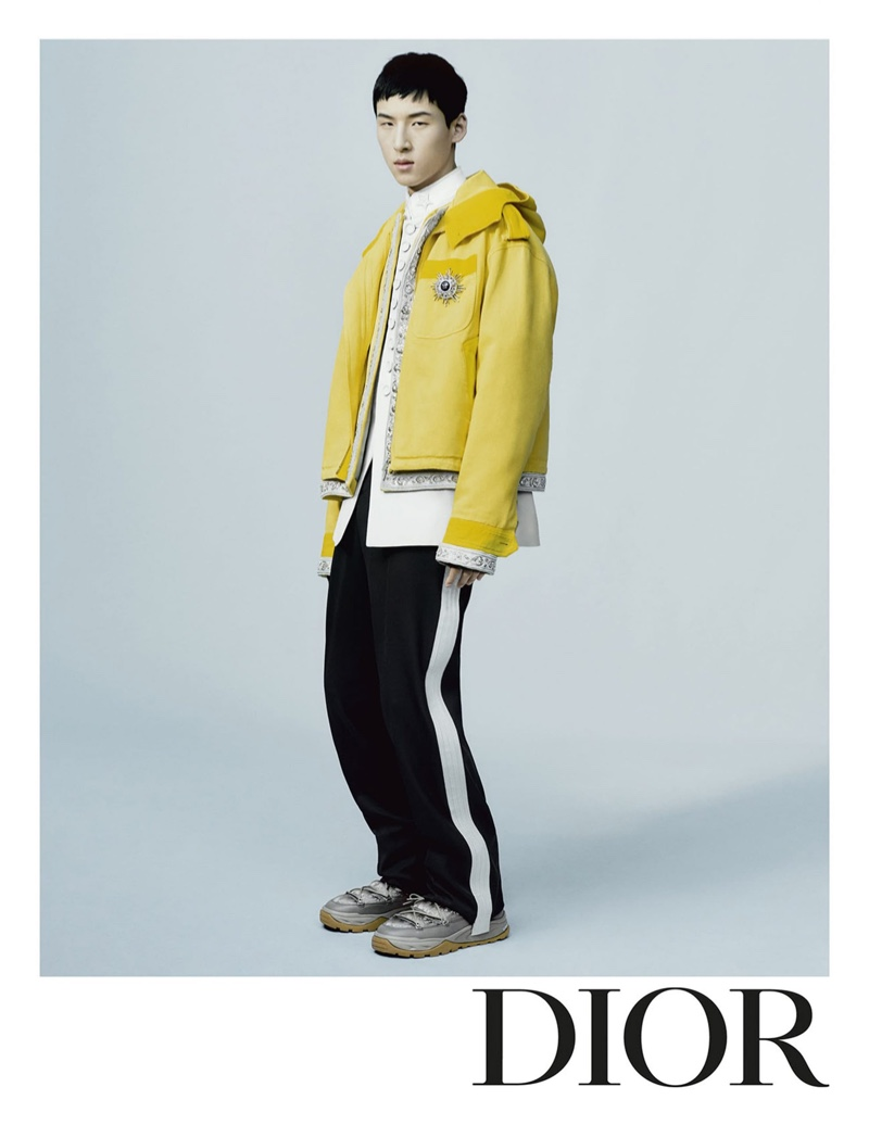 Woosang Kim is front and center for Dior Men's fall-winter 2021 campaign in a yellow hooded jacket with side stripe pants.