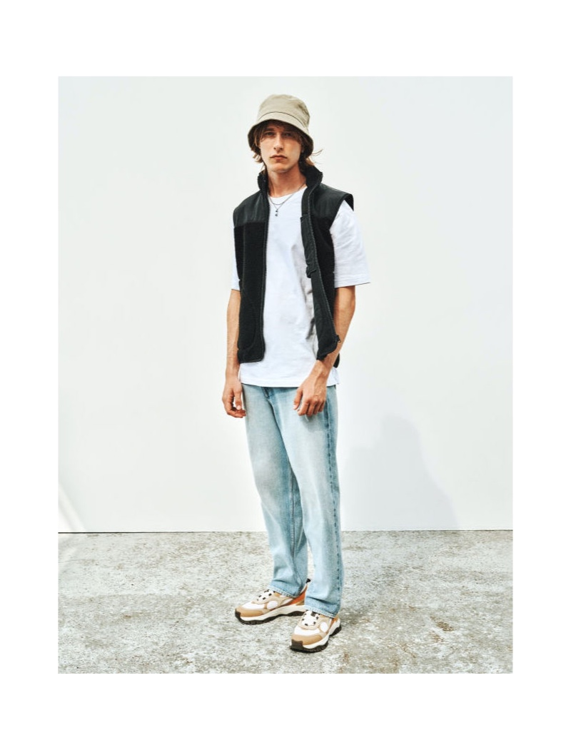 Front and center, Oscar Asberg models H&M's relaxed-fit denim jeans with a t-shirt and vest.