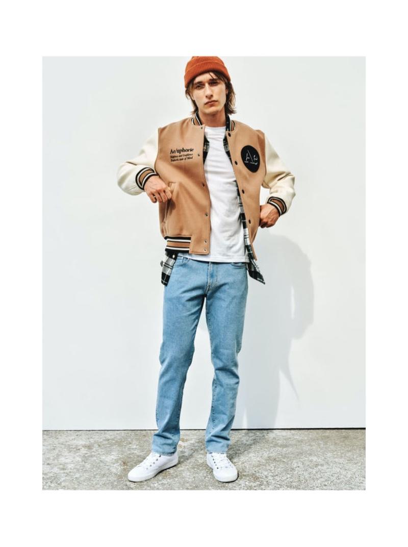 Oscar Asberg sports a varsity jacket with H&M Conscious regular jeans in light denim blue.