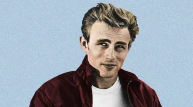 James Dean appears in a promotional image for Rebel Without a Cause (1955). The actor sports an iconic look consisting of a red Harrington jacket, white t-shirt, and Levi's jeans.