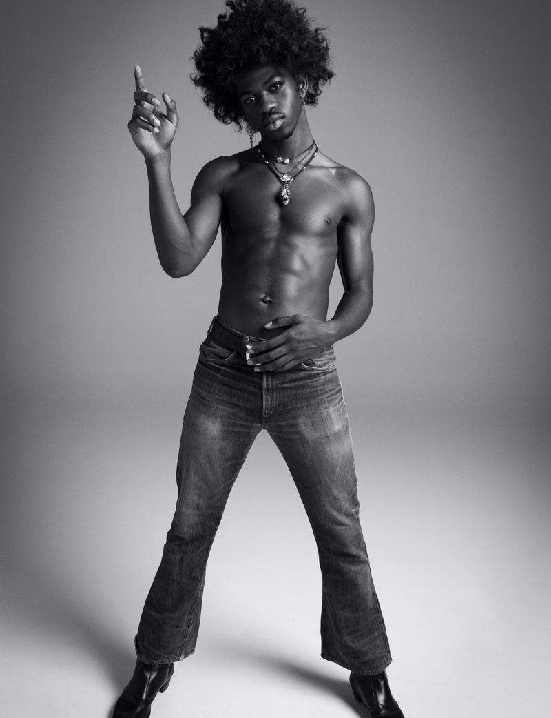 Going shirtless, Lil Nas X slips into a pair of vintage jeans as he channels Jimi Hendrix for VMAN.