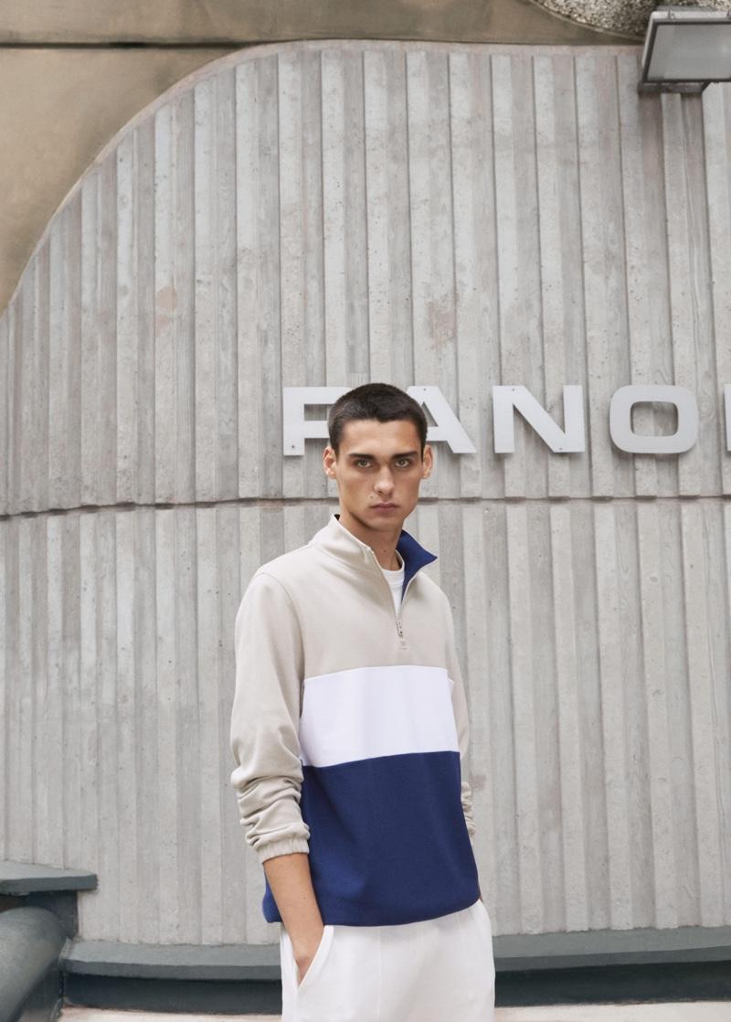 Embracing classic style, Ludwig Wilsdorff models a Mango Man color-block pique zip-neck sweatshirt.