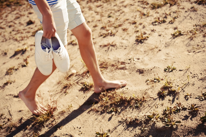 Man Holding Sneakers Walking Ground Barefoot