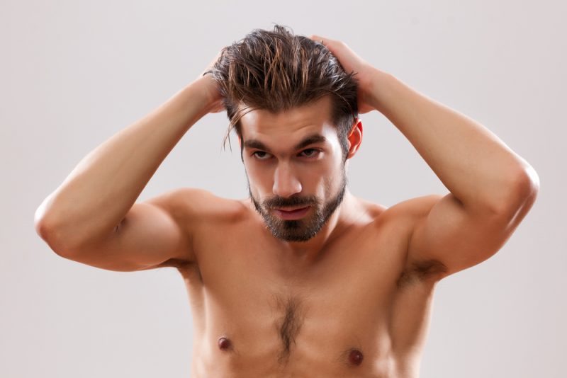 Man Looking at Hair in Mirror