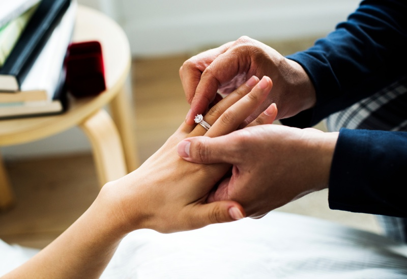 Man Placing Engagement Ring Womans Hand