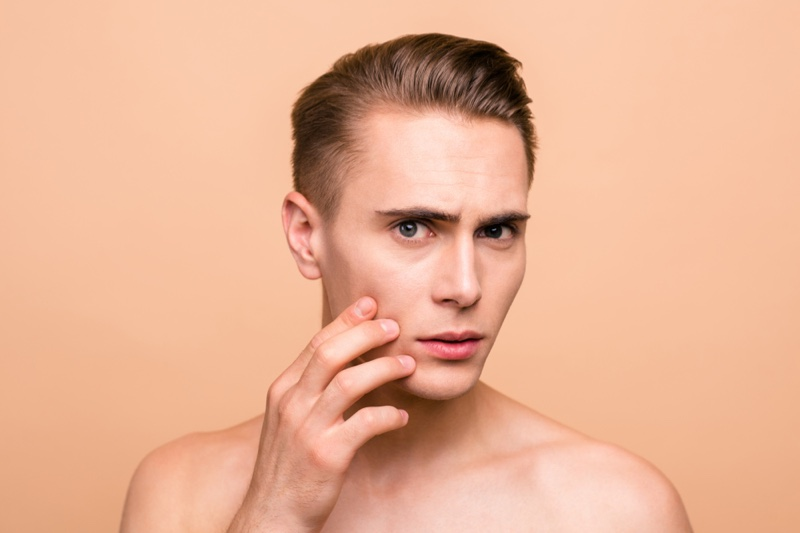 Man Worrying About Skin Touching Face