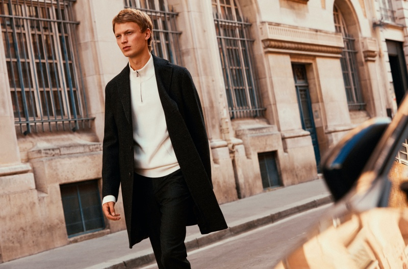 Model Jonas Glöer sports a Massimo Dutti coat with a half-zip pullover and pants.