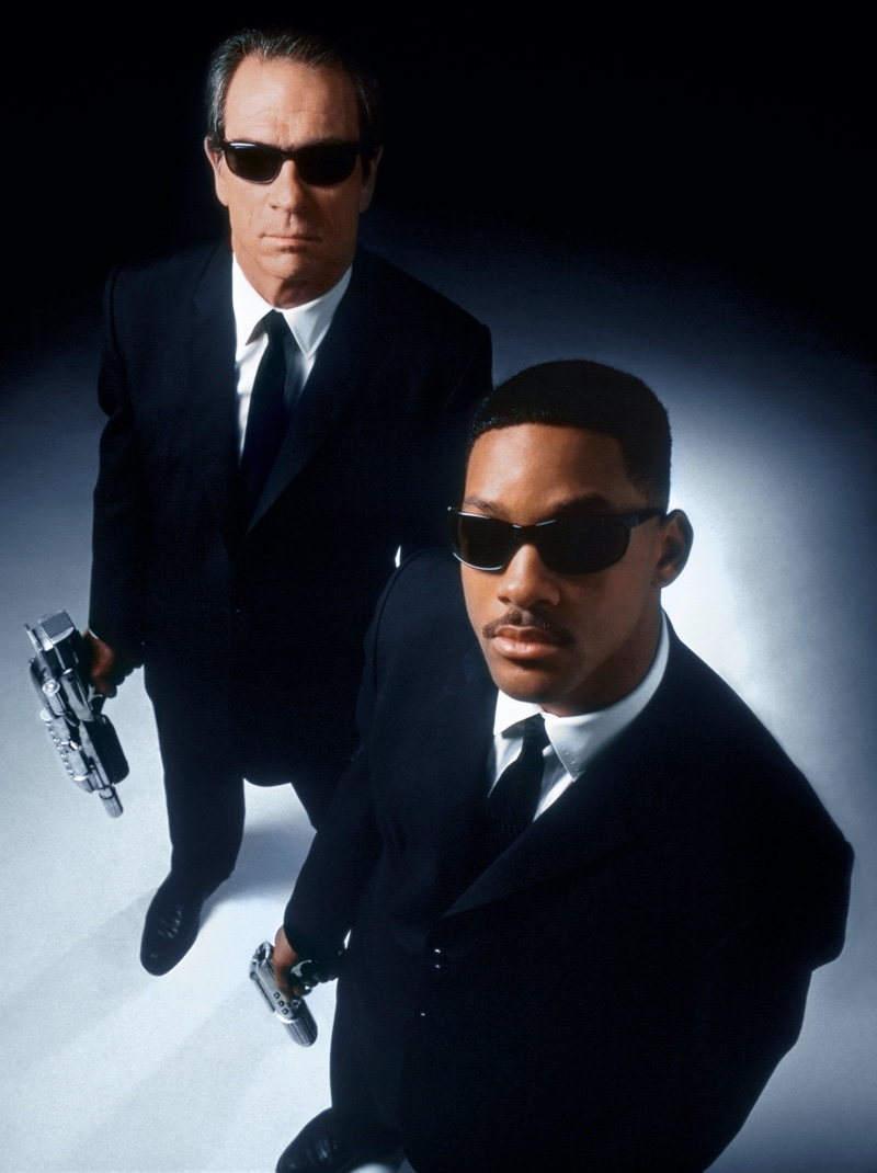 Tommy Lee Jones and Will Smith appear in a promotional image for Men in Black (1997). Nothing quite says secret agent like a uniform black suit and then you add sunglasses for an extra cool!