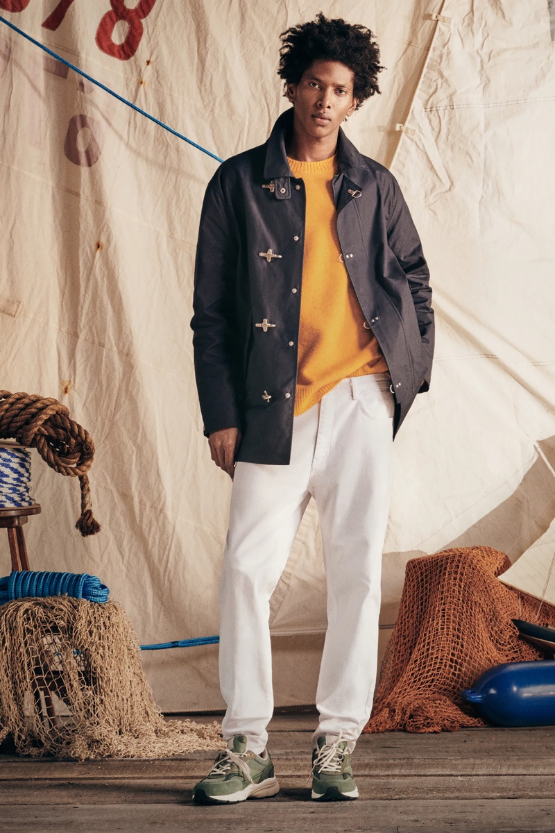 Rafael Mieses models white straight-fit jeans with a sweater and cotton pocket jacket by Zara.