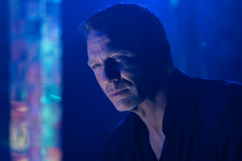 """In a still from """"No Time to Die,"""" Daniel Craig portrays James Bond as he wears a black Tom Ford shirt."""