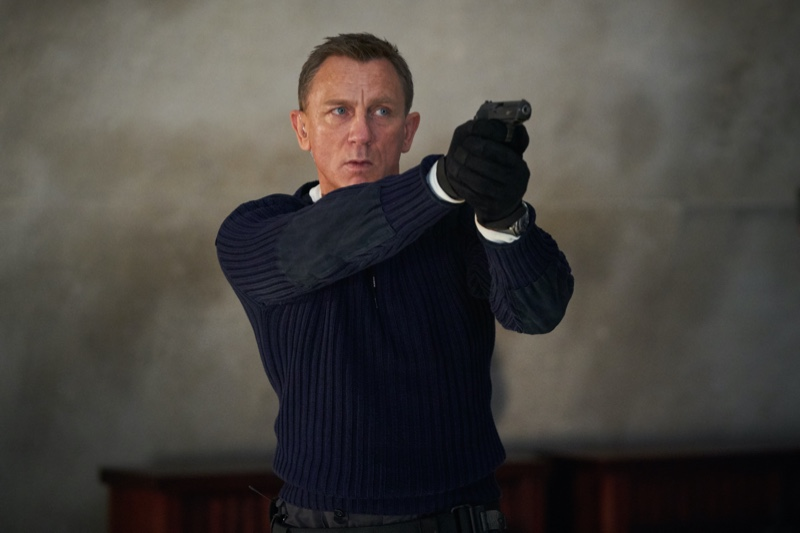 """Sporting a cable-knit sweater with elbow patches, Daniel Craig reprises his role as James Bond in a still from """"No Time to Die."""""""