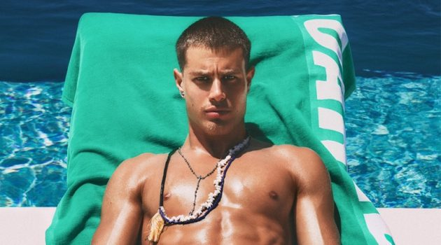 Working on his tan poolside, Roberto Hoshieh wears a green Dsquared2 swimsuit.
