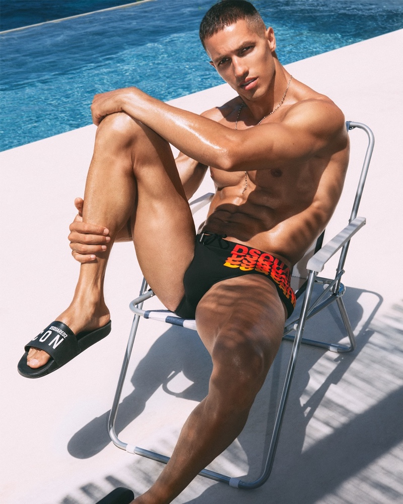 Christos Katsavochristos stretches in a black Dsquared2 swimsuit and ICON slides.