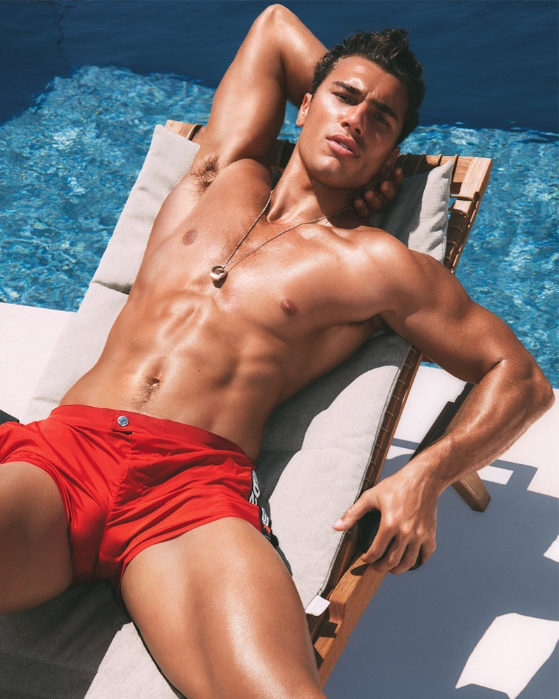 Deano Perona slips into a pair of red swim shorts for Dsquared2's beachwear campaign.