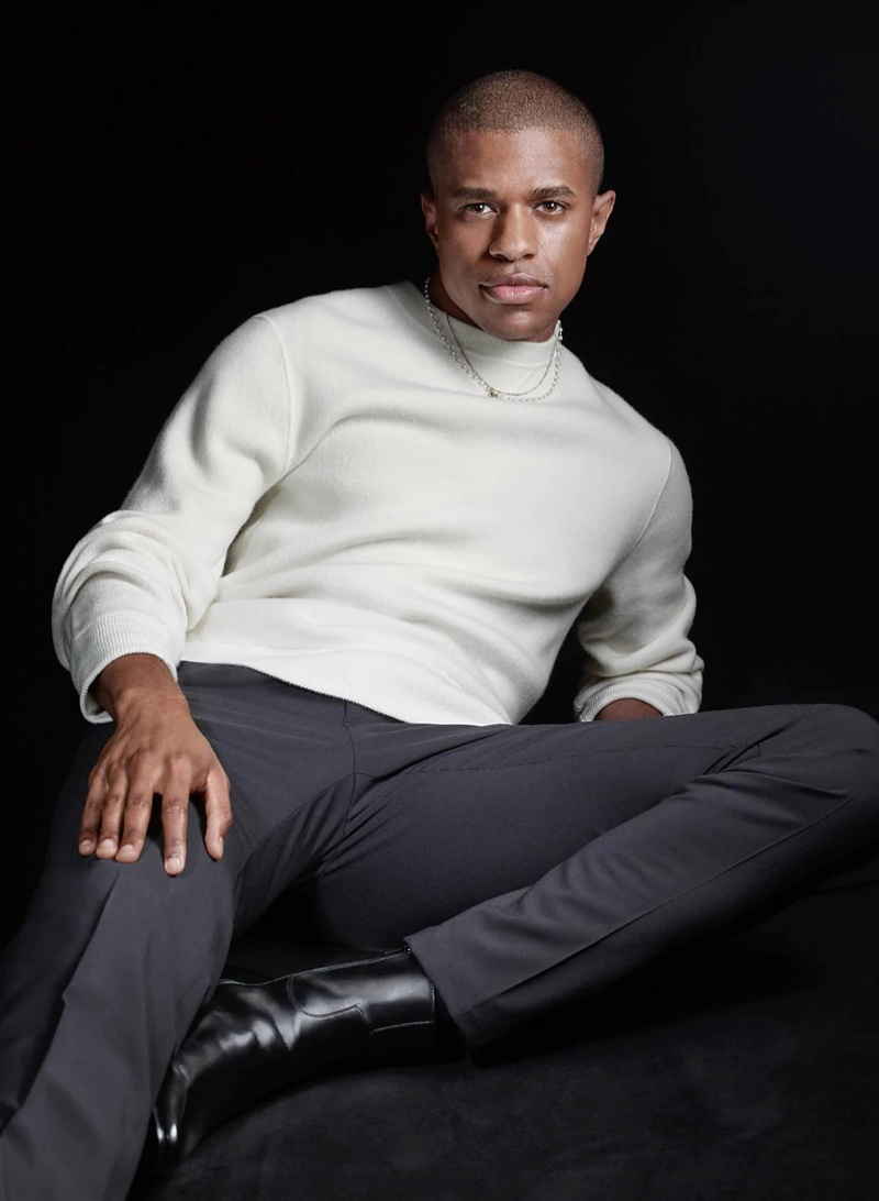 Actor Jeremy Pope wears a sweater with trousers and leather boots for Theory's fall-winter 2021 campaign.