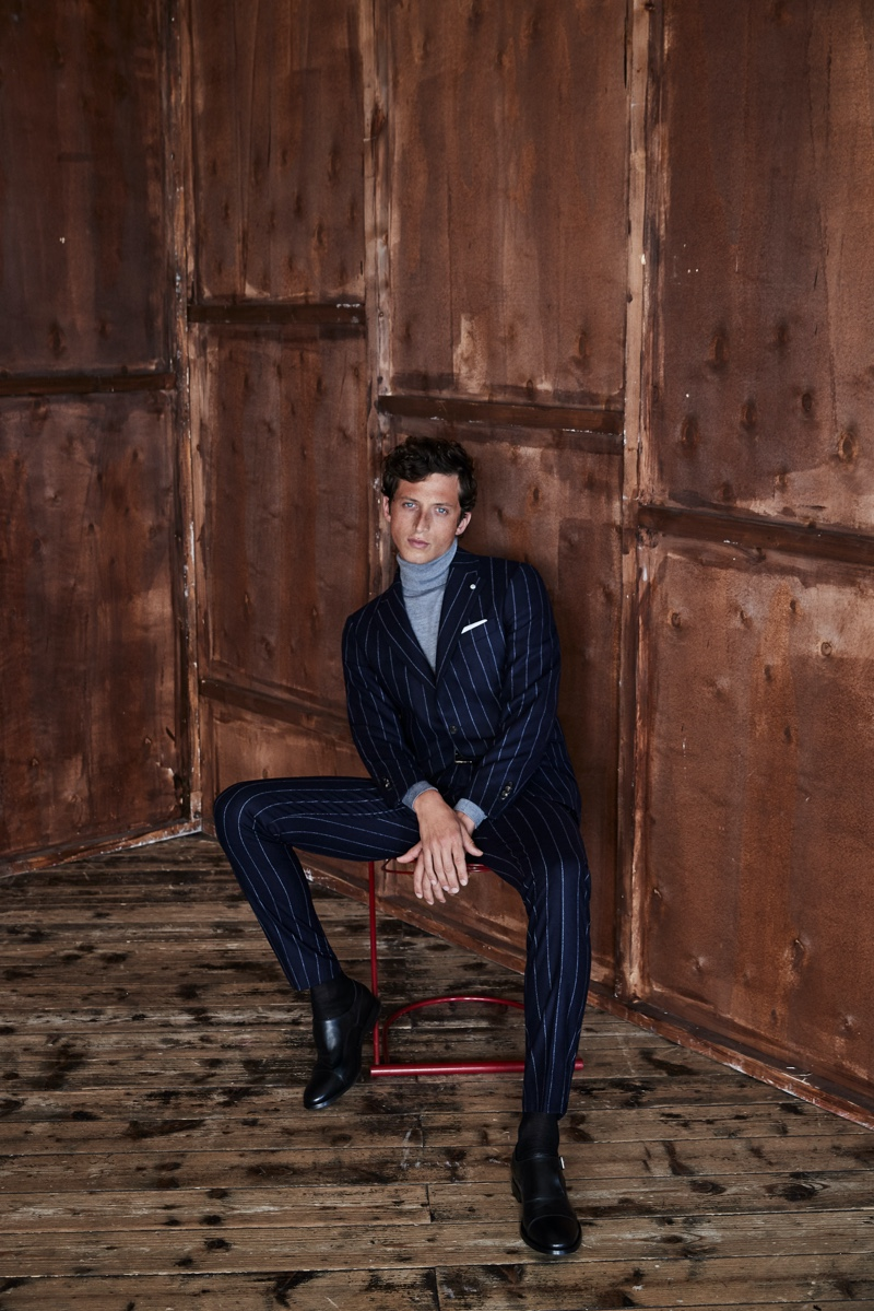 Alexis Maçon-Dauxerre dons a pinstripe suit with a turtleneck sweater from Luigi Bianchi Mantova's fall-winter 2021 collection.