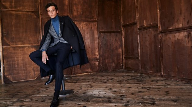 Donning a coat draped over his shoulders, Alexis Maçon-Dauxerre also models a check suit jacket and turtleneck from Luigi Bianchi Mantova.