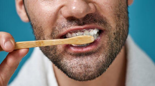 Man Brushing Teeth with Wooden Toothbrush Closeup