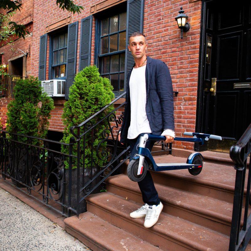 Man Carrying Unagi Electric Scooter