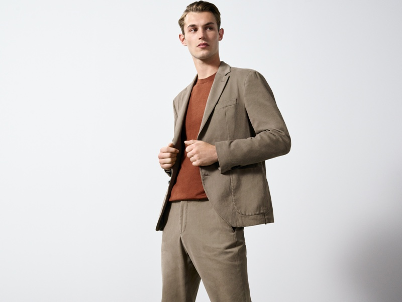 In front and center, Kit Butler dons a cotton slim-fit suit with a 100% merino wool sweater.