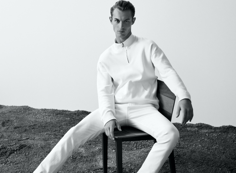 Dressed in white, Kit Butler wears a mock neck sweater with slim-fit jeans from Massimo Dutti's Join Life collection.