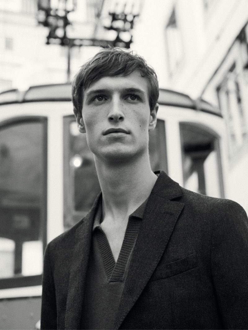 Appearing in a black and white photo, Egon Van Praet wears a v-neck polo sweater with a slim-fit wool flannel blazer from Massimo Dutti.