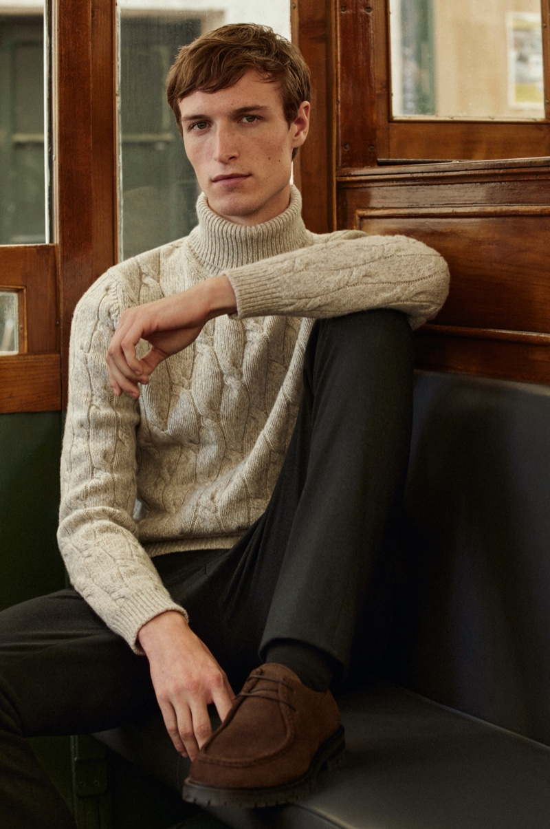 In front and center, Egon Van Praet models a Massimo Dutti cable-knit sweater with trousers.