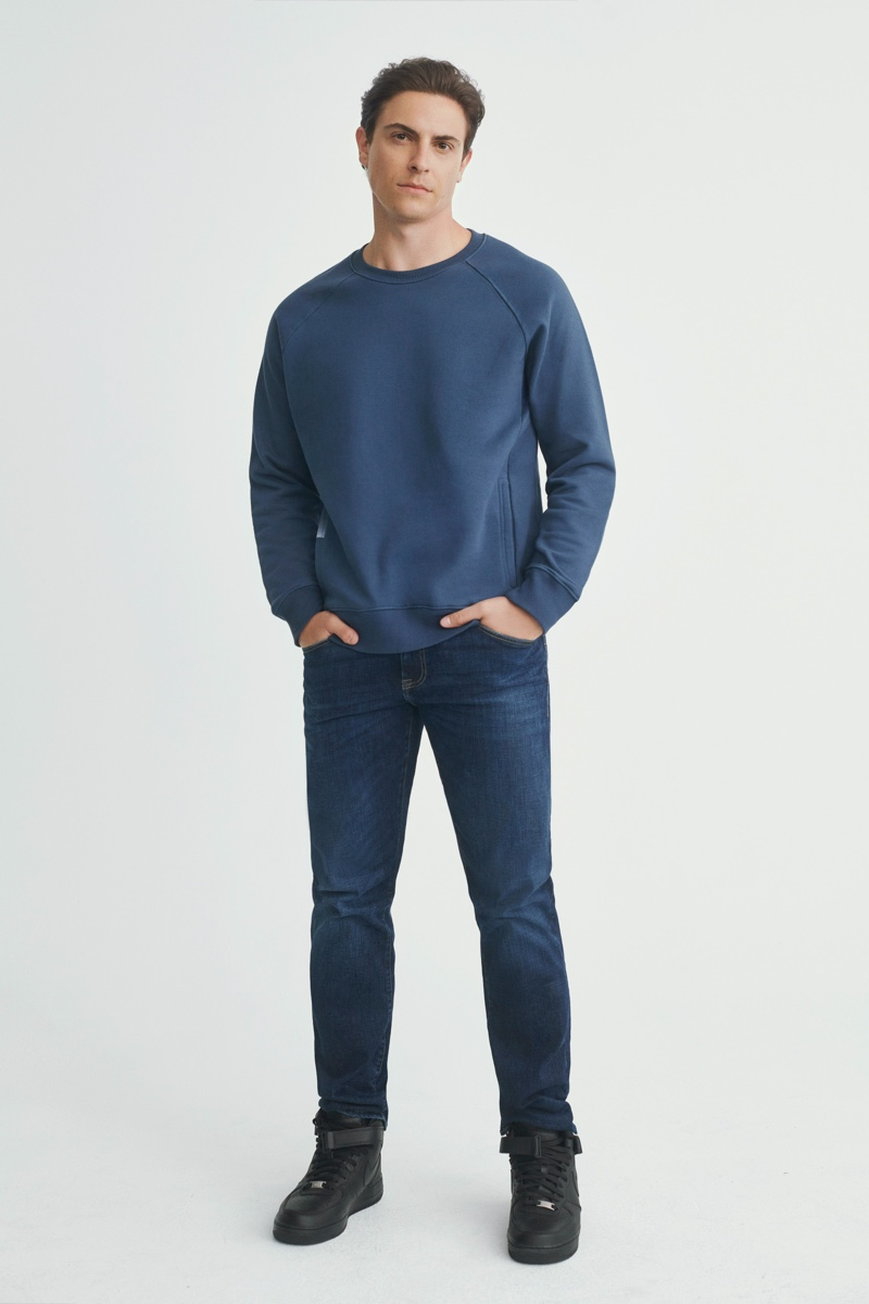 Actor Derek Klena wears a blue sweatshirt with jeans from Mavi's fall-winter 2021 collection.