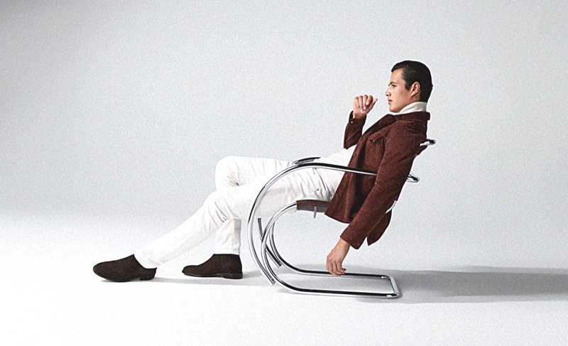 Relaxing in a modern chair, Harry Gozzett dons Reiss' must-have Florida rust suede twin pocket shirt with white jeans.