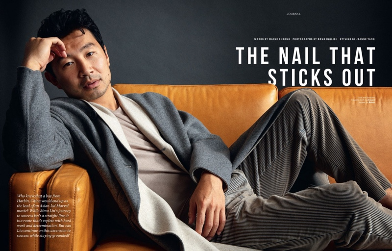 Lounging on a couch, Simu Liu wears an Armani coat and corduroy trousers with a Brioni sweater for Esquire Singapore.