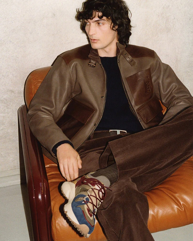 Donning a brown leather jacket with corduroy pants, Luca Lemaire showcases a new pair of sneakers for Tod's fall-winter 2021 men's campaign.