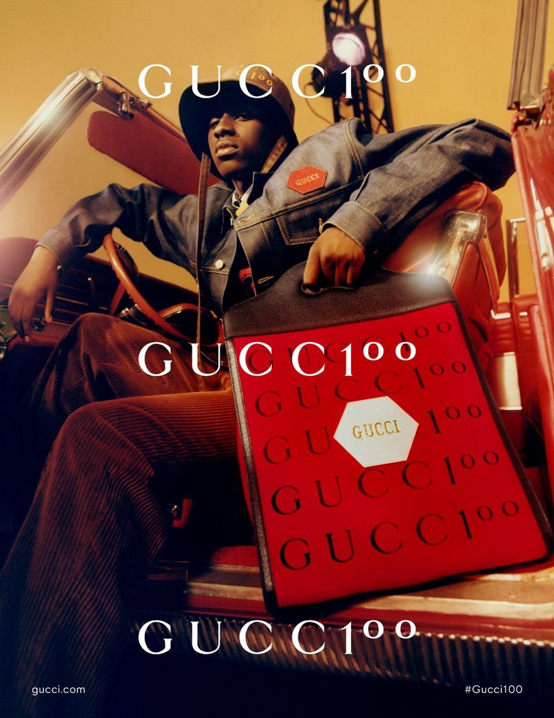 Cheikh Niang poses with an oversized shopper bag for the Gucci 100 campaign.